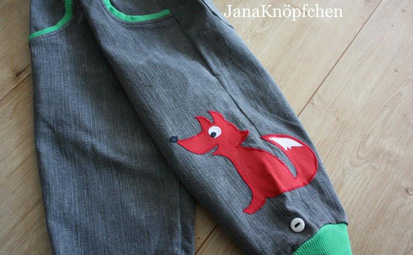 Kinderhose aus grauem Jeans mit grünem Bündchen. Das rechte Bein steht im Vordergrund und der Fuchs ist komplett zu sehen.